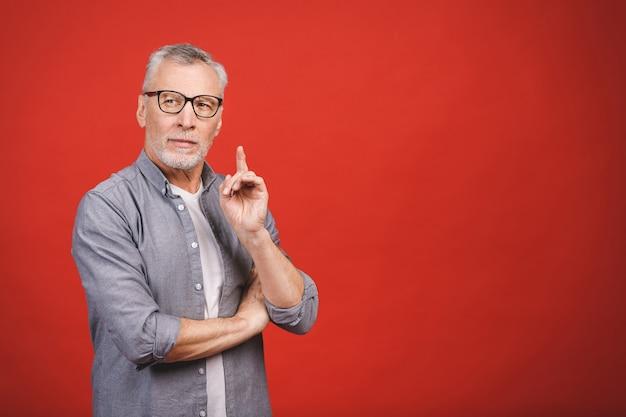 Mam świetny pomysł! portret dojrzały poważny biznesmen jest ubranym szkła odizolowywających przeciw czerwonemu tłu.