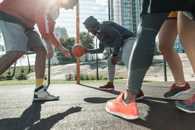 Mam to. darmowe zasady. silny miły mężczyzna bierze piłkę w ręce podczas gry w koszykówkę uliczną z przyjaciółmi