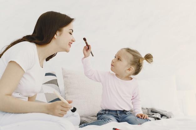 Mama bawi się kosmetykami w łóżku z córką