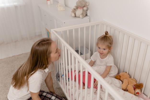 Mama bawi się z córką, córka siedzi w łóżeczku