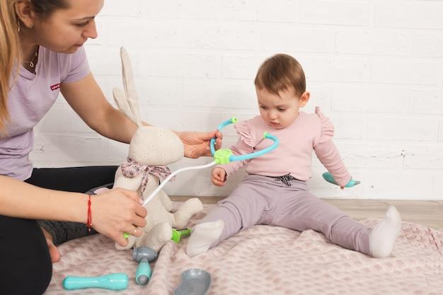 Mama bawi się z córką u lekarza w domu, siedząc na podłodze pojęcie medycyny