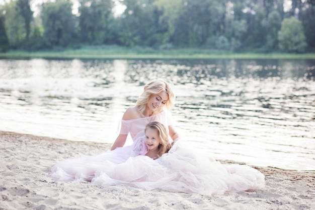 Mama bawi się z dzieckiem na wakacjach nad jeziorem. koncepcja życia rodzinnego i miłości. matka i córka ma czułych momenty outdoors. śliczna rodzina blisko wody. szczęśliwa kochająca rodzina.
