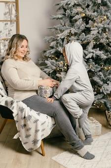 Mama bawi się z dzieckiem. szczęśliwa rodzina portret w domu w ciąży matka obejmuje swojego małego synka. szczęśliwego nowego roku. udekorowana choinka boże narodzenie poranek jasny salon kaukaska kobieta z dzieckiem