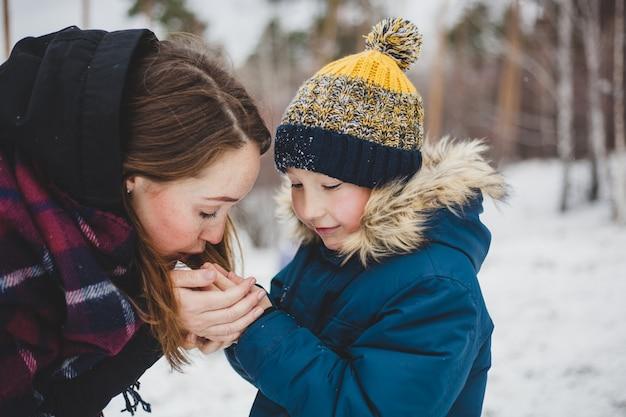 Mama całuje i ogrzewa dłonie swojego małego synka, spacerując po zimowym parku, spacerując, zimna, marznąc dłonie