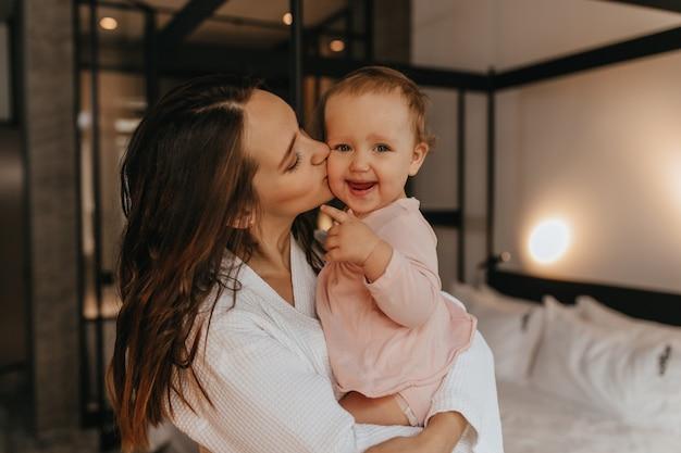 Mama całuje jasnowłosego dziecka patrząc na kamery z uśmiechem. kobieta trzyma córkę w ramionach na tle białego łóżka.
