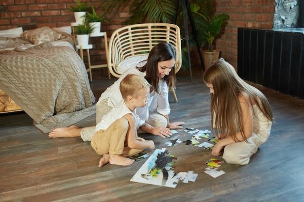 Mama, córka i syn układają puzzle na podłodze. rozrywka dla całej rodziny. kobieta, dziewczyna i chłopak grać razem