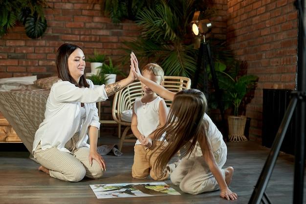 Mama, córka i syn układają puzzle na podłodze