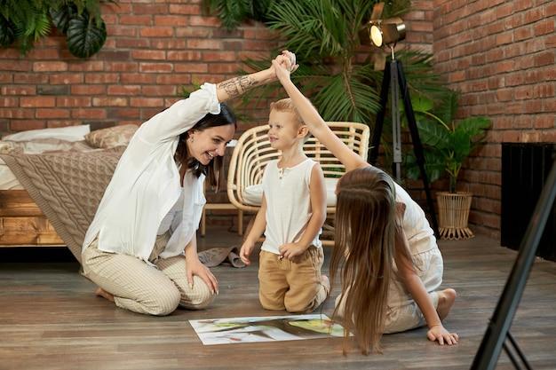 Mama, córka i syn układają puzzle na podłodze.