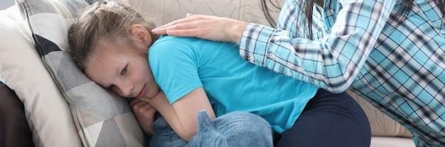 Mama głaszcząca plecy i pocieszająca małą dziewczynkę w domu