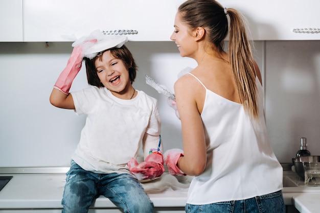 Mama gospodyni domowej w różowych rękawiczkach myje naczynia z synem ręcznie w zlewie z dodatkiem detergentu. dziewczynka w bieli i dziecko z gipsem sprząta dom i zmywa naczynia w domowych różowych rękawiczkach.