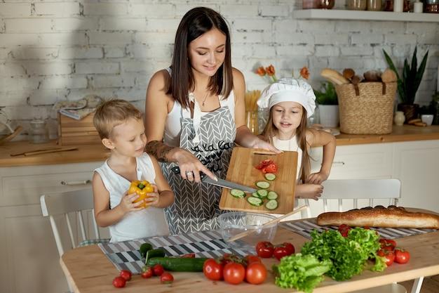 Mama gotuje obiad z dziećmi. kobieta uczy swoją córkę gotowania od swojego syna. wegetarianizm i zdrowa naturalna żywność