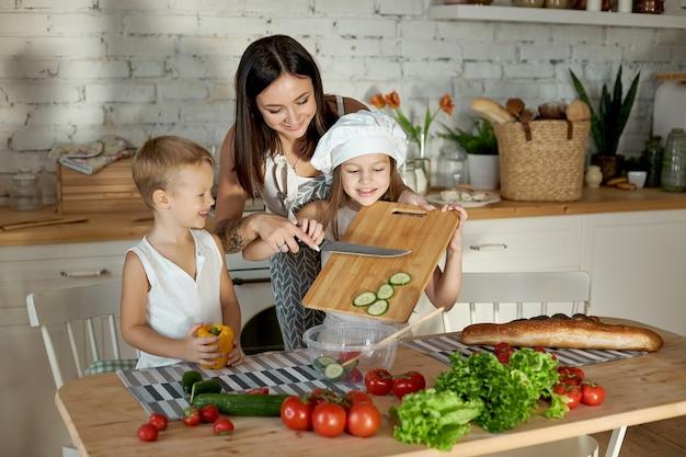 Mama gotuje obiad z dziećmi. kobieta uczy swoją córkę gotowania od swojego syna. wegetarianizm i zdrowa, naturalna żywność