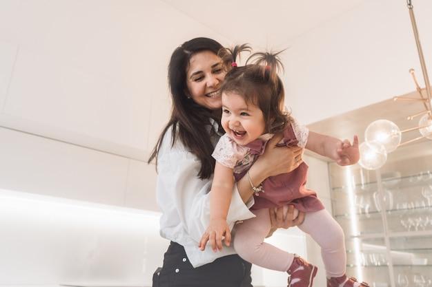 Mama gra z córką w aktywne gry. mama wymiotuje swoje dziecko. córka z mamą baw się dobrze