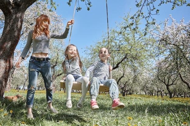 Mama huśta swoje córeczki na huśtawce ogrodowej