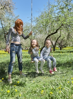 Mama huśta swoje dzieci na huśtawce ogrodowej