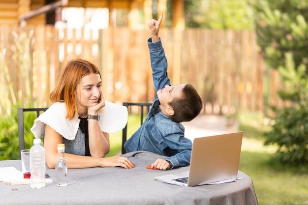 Mama i chłopiec uczeń są zaangażowani w lekcje przez laptopa w domu w ogrodzie. zajęcia online dla dzieci. chłopiec pojawia się w niebie