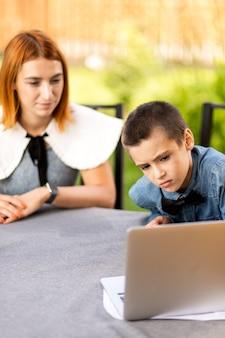 Mama i chłopiec uczeń są zaangażowani w lekcje przez laptopa w domu w ogrodzie. zajęcia online dla dzieci. uczeń słucha wykładu i rozwiązuje problemy