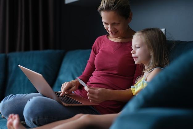 Mama i córeczka siedzą na kanapie z laptopem i kartą kredytową