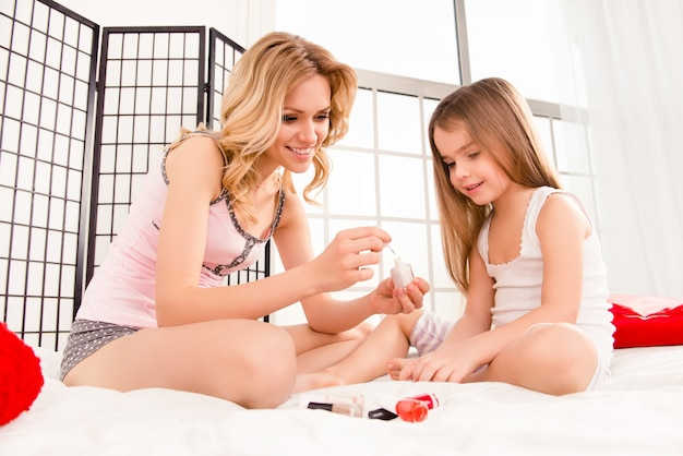Mama i córeczka siedzi na łóżku i maluje paznokcie