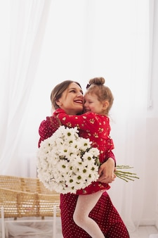 Mama i córeczka w czerwonych sukienkach w jasnej sypialni