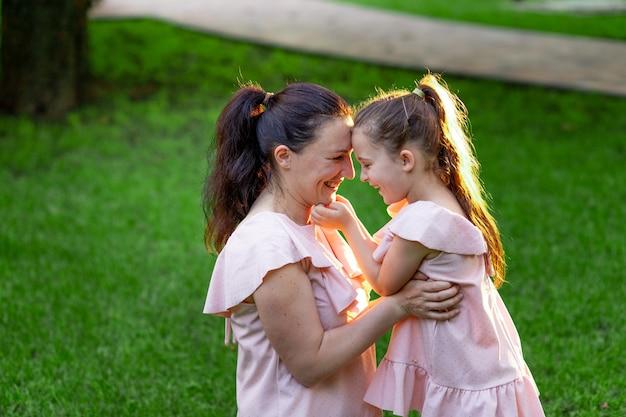 Mama i córka 5-6 lat siedzą latem w parku na trawie i śmieją się, rozmowa matka-córka