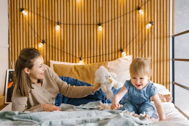 Mama i córka bawią się na łóżku i uśmiechają się. czas rodzinny w domu
