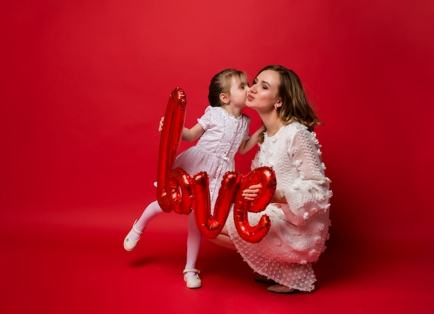 Mama i córka całują się i trzymają balon z folii powietrznej na czerwono