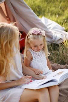 Mama i córka czytają książkę latem na pikniku. mama uczy córkę. zbliżenie. rozmyte tło