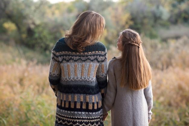 Mama i córka idą o zachodzie słońca. natura