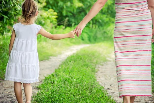 Mama i córka idą wzdłuż drogi trzymając się za ręce.