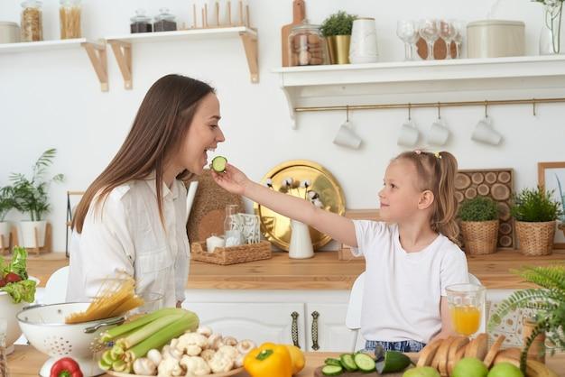 Mama i córka jedzą ogórki i śmieją się. prawidłowe odżywianie w domu. spędzać razem czas.
