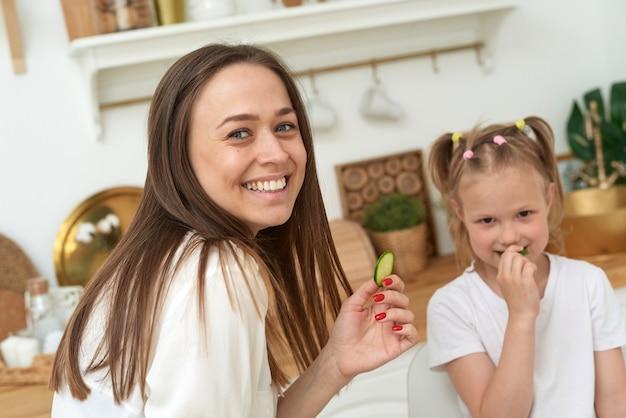 Mama i córka jedzą ogórki i śmieją się. prawidłowe odżywianie w domu.