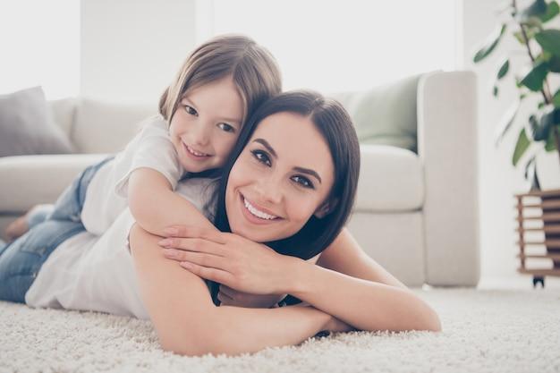 Mama i córka kładą dywan w salonie w pomieszczeniu
