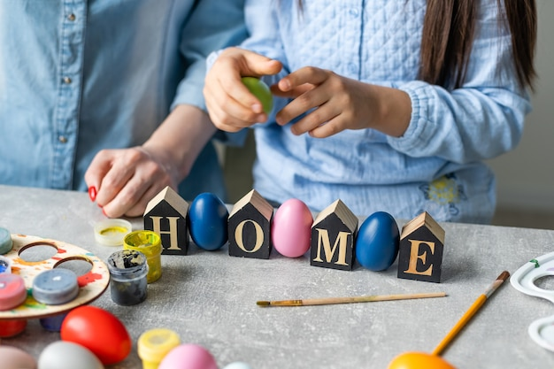 Mama i córka malują jajka kolorami. baw się dobrze. szczęśliwa rodzina przygotowuje się do wielkanocy, trzymaj napis do domu.