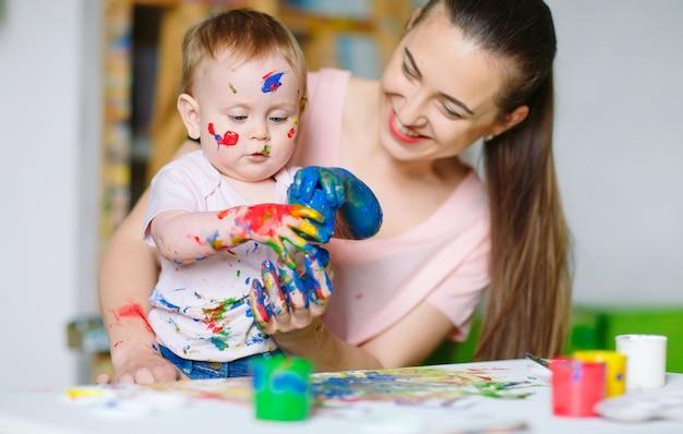 Mama i córka malują na płótnie w szkole rysunku.