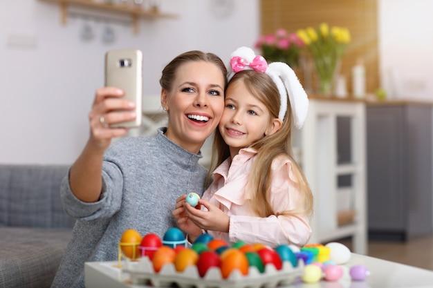 Mama i córka malują pisanki i robią sobie selfie