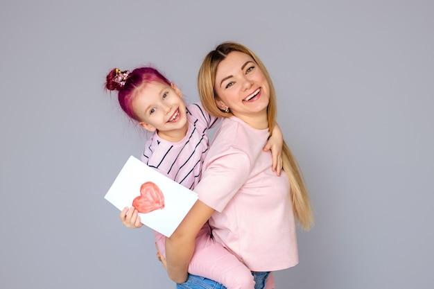 Mama i córka na białym tle na szarym tle portret. dzień matki koncepcja miłość dzieciństwo rodzina
