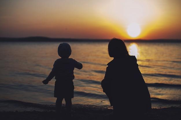 Mama i córka na plaży oglądając zachód słońca
