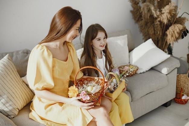 Mama i córka przygotowują się do wielkanocy w domu na kanapie w żółtych ubraniach