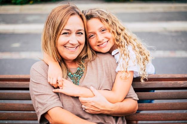 Mama i córka przytulają się razem z miłością i szczęściem na ławce w czasie wolnym na świeżym powietrzu - rodzina z kaukaską kobietą i dziewczyną ludzie wesoły