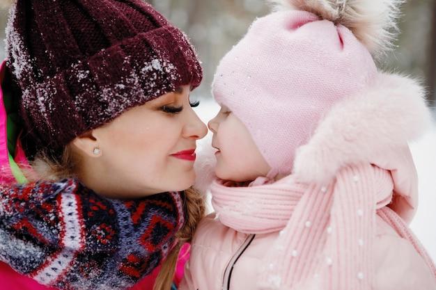 Mama i córka przytulają się w zaśnieżonym parku zimą na świeżym powietrzu.