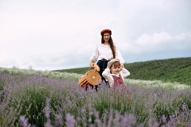 Mama i córka razem zbierają kwiaty lawendy w koszu.