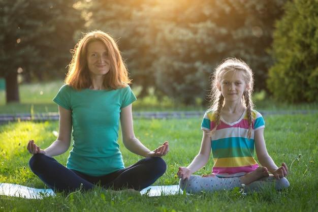 Mama i córka robią jogę w parku