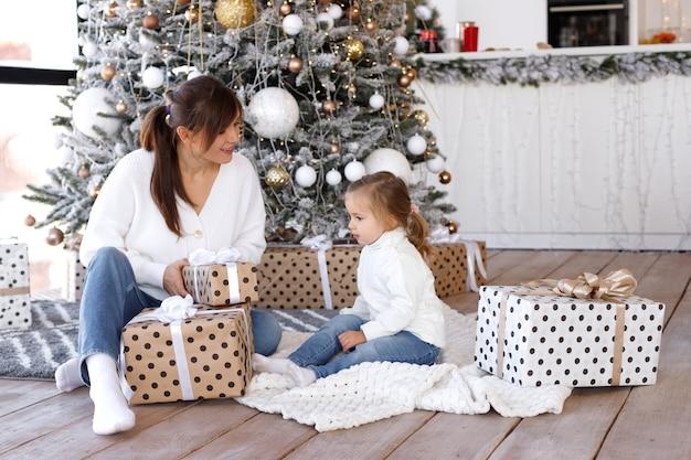Mama i córka rozpakowują prezenty na boże narodzenie