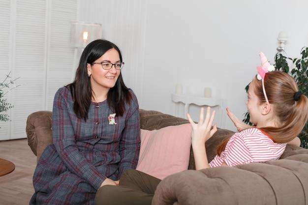 Mama i córka siedzą na kanapie i rozmawiają. nastolatka z emocjami opowiada historię swojej matki