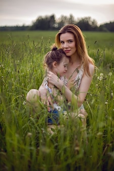 Mama i córka siedzą w zielonym polu w białej koszulce