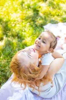 Mama i córka śmieją się i przytulają siedzą na kocu w parku koncepcja szczęśliwej rodziny...