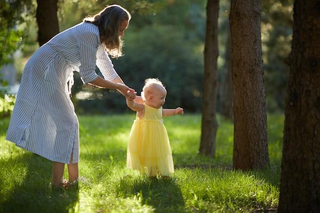 Mama i córka spacerują po słonecznym parku w letni dzień. skopiuj miejsce.