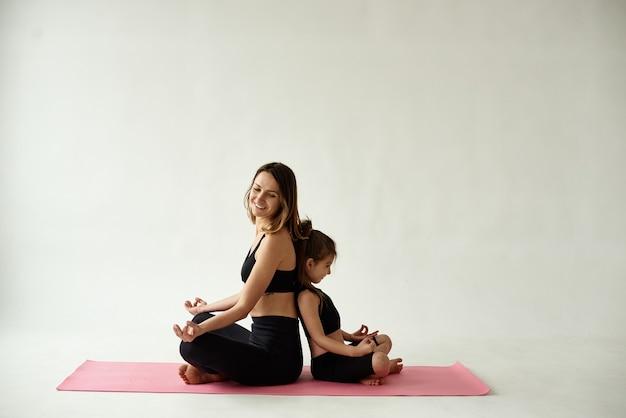 Mama i córka spędzają poranną praktykę jogi.