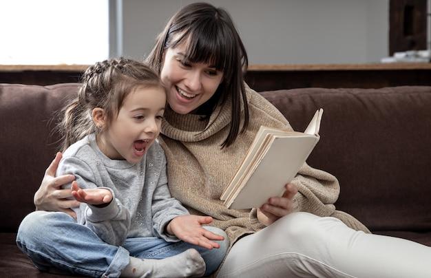 Mama i córka spędzają razem czas czytając książkę. pojęcie rozwoju dzieci i jakości czasu.